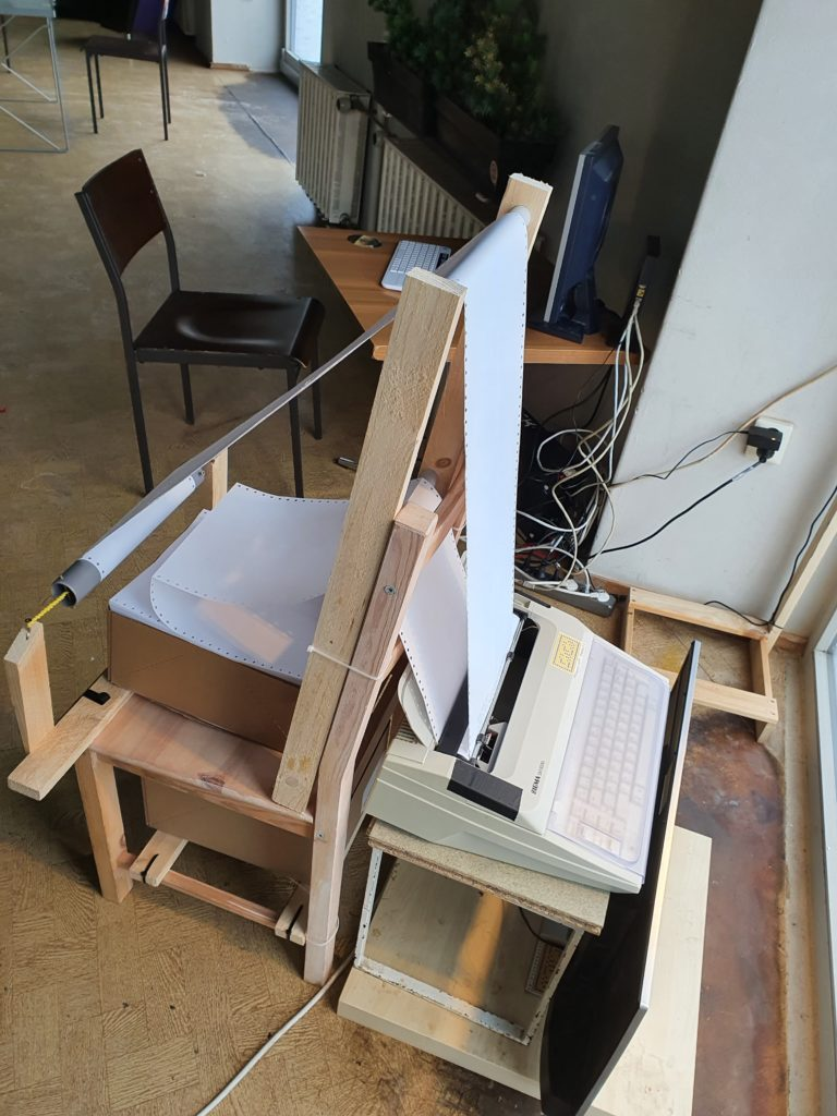 Schreibmaschine mit Papierführung über einen Stuhl